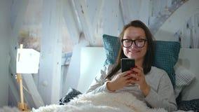De vrouw in glazen ligt in een bed en gebruikt een smartphone vóór bedtijd stock video