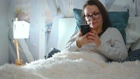 De vrouw in glazen ligt in een bed en gebruikt een smartphone vóór bedtijd stock footage