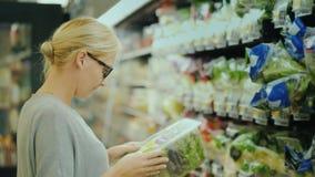 De vrouw in glazen selecteert producten in de afdeling van supermarkt verse groenten stock videobeelden