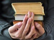 De vrouw in grijze kleren houdt oude boeken in hand stock afbeelding