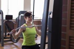 De vrouw in de gymnastiek, heft de lading op royalty-vrije stock foto