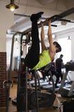 De vrouw in de gymnastiek, schudt de pers op de bar stock foto