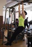 De vrouw in de gymnastiek, schudt de pers op de bar stock afbeelding