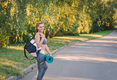 De vrouw in haar fitness park met sporten doet op zijn schouder en pa in zakken Stock Foto's
