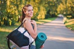 De vrouw in haar fitness park met sporten doet op zijn schouder en pa in zakken Royalty-vrije Stock Afbeeldingen