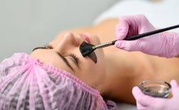 De vrouw in haarnetje ligt en ontspant op laag in schoonheidssalon terwijl de arts begint donkere klei op haar gezicht toe te pas stock afbeeldingen