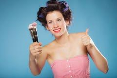 De vrouw in haarrollen houdt make-upborstels Stock Afbeeldingen