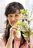 De vrouw hangt paasei op kersentak. Stock Foto
