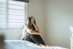 De vrouw heeft een hoofdpijn en omhoog het voelen van droefheid op bed na kielzog in de ochtend Royalty-vrije Stock Afbeeldingen