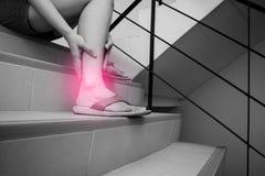 De vrouw heeft kalfsklem en wat betreft gekwetst been tijdens onderaan treden gaan Zwart-witte toon met rode vlek bij haar been stock afbeeldingen