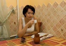 De vrouw heeft koffie op keuken Stock Afbeeldingen