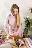 De vrouw heeft pak feestelijk boeket in verpakkend document Royalty-vrije Stock Fotografie