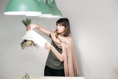 De vrouw heeft pak feestelijk boeket in verpakkend document De jonge mooie bloemist maakt floristry met roze pioen assembleren en Stock Afbeelding