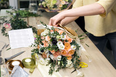 De vrouw heeft pak feestelijk boeket in verpakkend document De jonge mooie bloemist maakt floristry met roze pioen assembleren en Royalty-vrije Stock Foto's