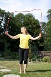 De vrouw heeft pret met touwtjespringen Stock Fotografie