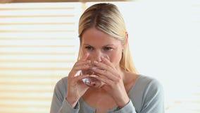 De vrouw heft een glas water van een lijst op stock video
