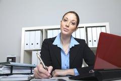 De vrouw in het bureau maakt een nota Stock Afbeeldingen