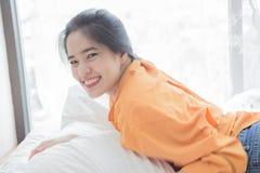de vrouw is het gelukkige liggen op bed Royalty-vrije Stock Afbeeldingen