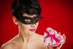 De vrouw in het masker bekijkt een gift Royalty-vrije Stock Afbeeldingen