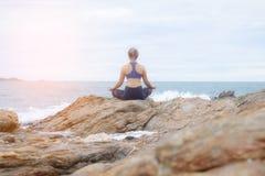 De vrouw het praktizeren yogazonsondergang op het strand Stock Foto