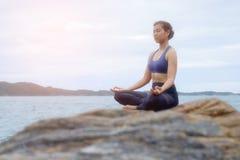 De vrouw het praktizeren yogazonsondergang op het strand Royalty-vrije Stock Afbeeldingen