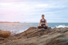 De vrouw het praktizeren yogazonsondergang op het strand Stock Foto's