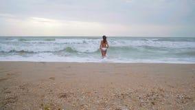 De vrouw in het witte zwempak komt aan het overzees tijdens de tijd van onweer stock video