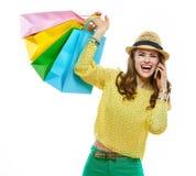 De vrouw in hoed met het winkelen doet zich sprekende cel telefoon en het verheugen in zakken stock foto's