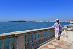 De vrouw in hoedenplanken die op balustrade leunen en bekijkt de stad van Venetië Royalty-vrije Stock Afbeelding