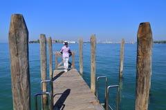 De vrouw in hoedenplanken die op balustrade leunen en bekijkt de stad van Venetië Royalty-vrije Stock Afbeeldingen