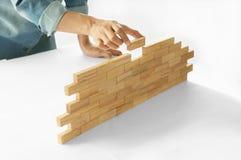 De vrouw in de holding van het jeansoverhemd blokkeert houten spel & x28; jenga& x29; De bouw a Stock Afbeelding
