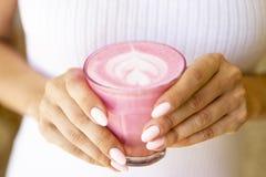 De vrouw houdt bieten latte met witte kledingsachtergrond stock afbeeldingen