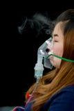 De vrouw houdt de behandeling van het maskerinhaleertoestel van astma stock afbeelding