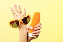 De vrouw houdt de lotion van het zonnebrilzonnescherm Stock Foto's
