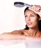 De vrouw houdt douche in handen met dalend water Stock Foto's
