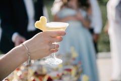 De vrouw houdt een glas met drank in hand dichte omhooggaand stock afbeelding