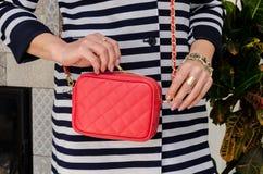 De vrouw houdt een kleine modieuze zakkoppeling van helder rode kleurenverstand stock fotografie