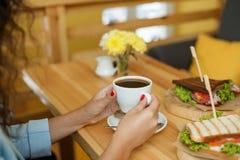 De vrouw houdt een kop van koffie bij backgroud houten lijst, waarop een sandwich ligt royalty-vrije stock foto's