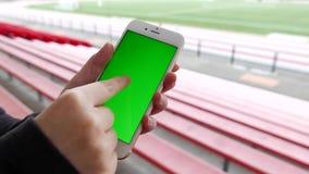 De vrouw houdt een leeg slim apparaat met het groen scherm bij ingediende sport stock video