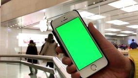 De vrouw houdt een leeg slim apparaat met het groen scherm voor uw eigen douaneinhoud stock videobeelden