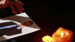 De vrouw houdt een ritueel van zwarte kunst werktijdmensen Hij gebruikt fotografie de vinger port een naald stock video