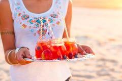De vrouw houdt een schotel met dranken bij zonsondergang Picknickthema royalty-vrije stock afbeelding