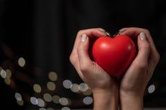 De vrouw houdt groot rood hart in haar hand stock foto