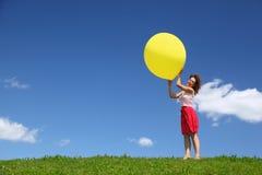 De vrouw houdt grote bal in handen op wind Royalty-vrije Stock Afbeeldingen