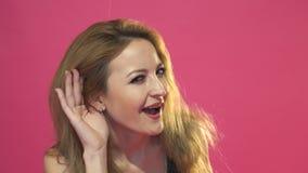 De vrouw houdt haar hand dichtbij oor en luistert zorgvuldig geïsoleerd op roze muurachtergrond stock videobeelden