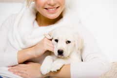 De vrouw houdt het puppy van Labrador op haar handen royalty-vrije stock afbeelding