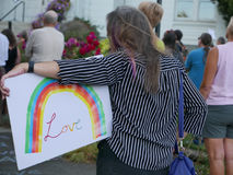 De vrouw houdt `-het teken van de LIEFDE` regenboog bij politieke verzameling Stock Afbeeldingen