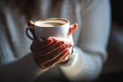 De vrouw houdt hete kop van koffie, die haar handen verwarmen Stock Foto's