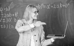 De vrouw houdt laptop richtend met wapengebaar op het scherm Opvoeder slimme slimme dame met modern laptop greepkanon stock afbeeldingen
