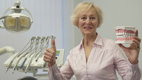 De vrouw houdt lay-out van menselijke tanden stock video
